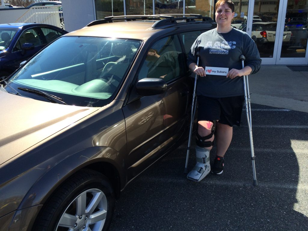 lady with crutches standing next to a brown car, holding a sign