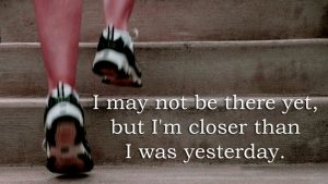 "human legs with running shoes on running up steps with words: ""I may not be there yet, but I'm closer than I was yesterday"""